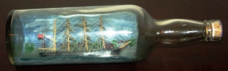 Early 20th century sailor-made ship model housed in bottle depicting a Danish 4-masted barque.