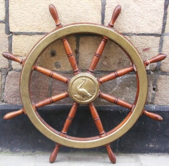 Late 19th century eight-spoked mahogany ships wheel with double brass bands and a central brass hub decorated with a casted swan