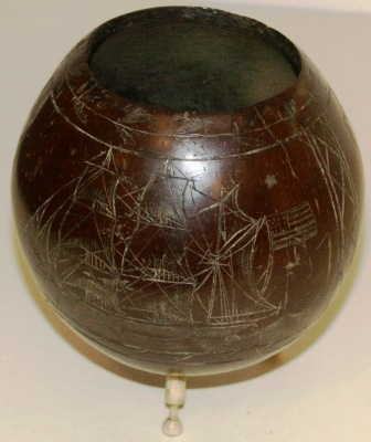 Late 19th century sailor-made carved coconut shell. Decorated with three motifs and mounted on carved whale bone pins.