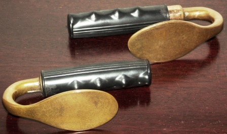 A pair of 20th century cuff spoons. Brass, rubber-dressed handles. Made by Siebe Gorman.