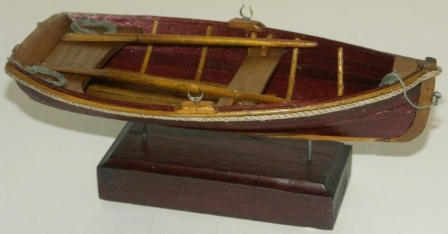 20th century clinker-built wooden dinghy, mounted on wooden base.