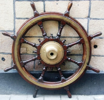 Late 19th century eight-spoked mahogany ships wheel with double brass bands and central brass hub.