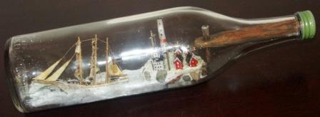 Early 20th century sailor-made ship model housed in bottle. Depicting a Swedish 3-masted barque with lighthouse and lightkeeper houses.