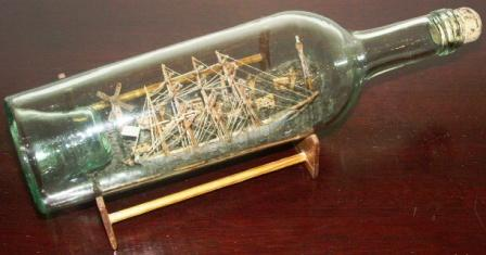 Late 19th century sailor-made ship model housed in bottle depicting a Swedish 4-masted barque. Incl wooden stand