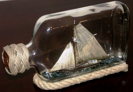 "20th century ship model housed in bottle depicting ""Vedjakten ELVIRA 1857"", a traditional Swedish archipelago sloop carrying wood. Signed GF (Göran Fors)."