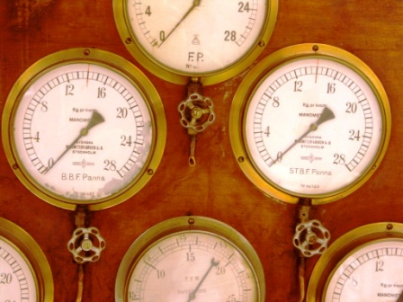 20th century pressure gauges in brass mounted on wooden panel