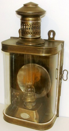 Early 20th century kerosene bulkhead lamp in brass. With detachable burner/container. Made by J. C. Larsén & Co, Österlånggatan 43 Stockholm.