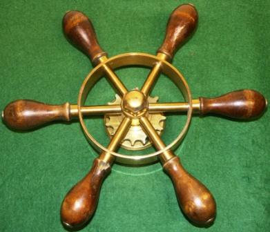 20th century six-spoked brass steering wheel with mahogany handles.