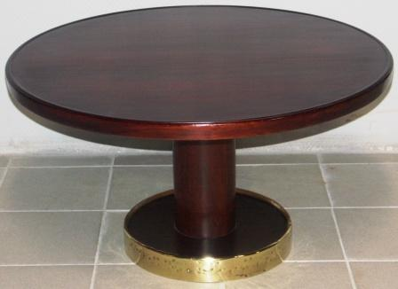 Round coffee table in mahogany. Base mantled with brass.