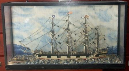 Early 20th century sailor-made model depicting a four-masted barque, cable ship and rowing boat. Mounted in glass case.