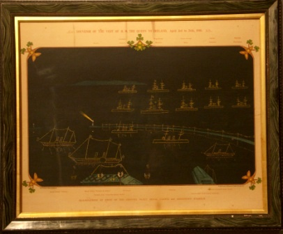 Original print commemorating H.M. the Queens visit to Ireland, April 3rd to 26th 1900. Depicting illuminations at night of the Channel Fleet, Royal yachts and Kingston Harbour. Including the Royal Yachts Osbourne and Victoria & Albert as well as the Harbour Commissioners Yacht. Also including the fleet vessels Howth, Australia, Galatea, Magnificent, Majestic, Prince George, mars, Jupiter, Hannibal, Repulse, Resolution, Melampus adn Pactolus. Further depicting Victoria Pier where the Queen landed and Carlisle Pier & Holyhead Mailboat.