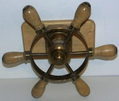 Mid 20th century six-spoked brass steering wheel with oak handles. Mounted on wooden base.