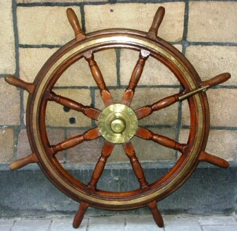 Late 19th century eight-spoked ships wheel. Made of mahogany. With double brass bands and central brass hub.