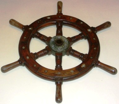 20th century six-spoked laquered oak ships wheel. With brass band and central brass hub.