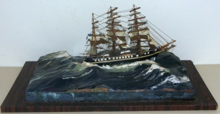 20th century built waterline model depicting a full-rigged vessel in heavy sea. With working crew aloft. Signed H.B. 1968. Mounted in glass case.