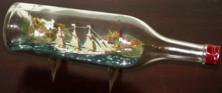 Early 20th century sailor-made ship model housed in bottle depicting a schooner with set sails. Incl metal stand.