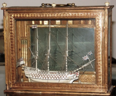 A very fine and detailed early 19th century prisoner-of-war bone model of a 98-gun ship-of-the-line. Mounted in wooden carrying case applied with coloured straw, also made by prisoners-of-war. Furnished with mirrored back panel to inspect the far side of the model.