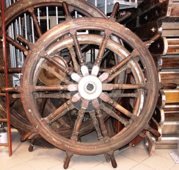 Late 19th century ten-spoked ships wheel. Made of teak. With double brass bands and central brass hub.