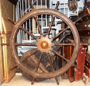 Late 19th century ten-spoked ships wheel. Made of teak. With double brass bands and central iron hub with brass casing.