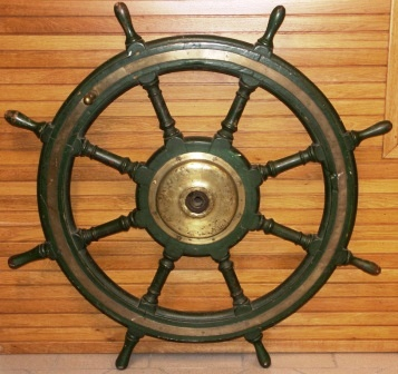 Early 20th century eight-spoked greenpainted ships wheel. Made of oak. With double brass bands and central brass hub.