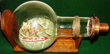 "Early 20th century ships in light bulb, mounted on wooden stand. With engraved brass plate documenting: ""This bulb has lit Flamborough Head Light for 1,000 hrs., then taken out of service"" ."