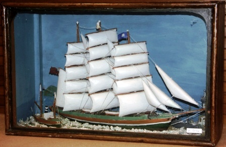 Late 19th century sailor-made diorama. Depicting a fullrigged ship together with a pilot-boat, a naval vessel and a lighthouse. Mounted in origianal case.