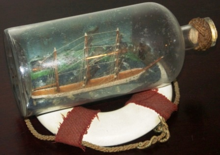 Late 19th century sailor-made ship model housed in bottle depicting a 3-masted barque. Incl lifebuoy-stand.